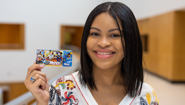Artist Nehemiah holds up the new Black American Heritage Library Card, which she designed.