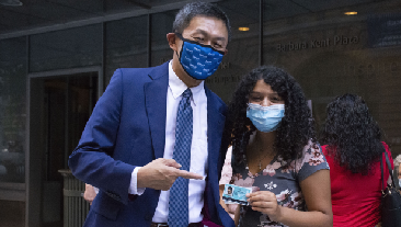 President Wu stands with a student who is holding her new ID